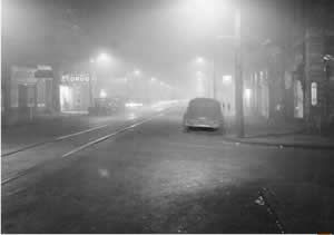 A street scene at noon in Donora, 1948, where streetlights were needed because of low visibility from smog.